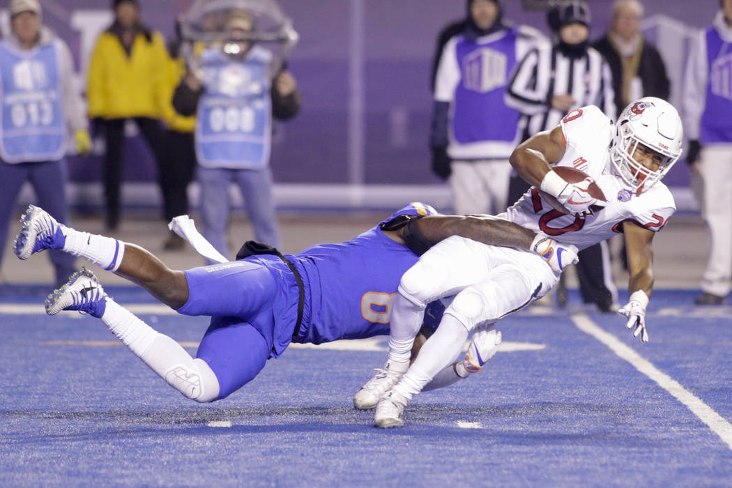 Fresno State running back Ronnie Rivers (20) is brought down by Boise State defensive end Jabril Frazier (8) during the first half of an NCAA college football game for the Mountain West championsh ...