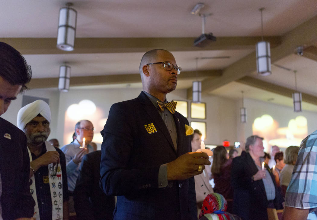 Senator Aaron Ford holds a candle during a moment of silence in a vigil for peace and unity and for Las Vegans to stand shoulder-to-shoulder in denouncing anti-Semitism, racism and bigotry  at the ...