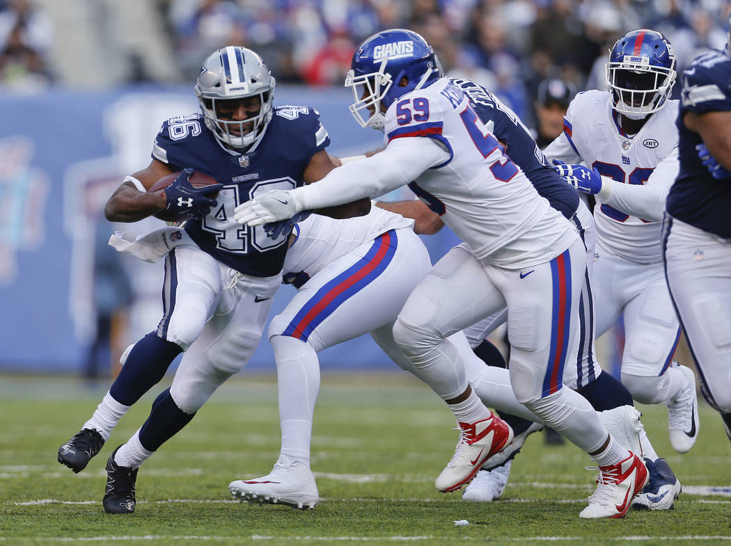 Dallas Cowboys running back Alfred Morris (46) runs the ball against New York Giants outside linebacker Devon Kennard (59) during the first quarter of an NFL football game, Sunday, Dec. 10, 2017,  ...