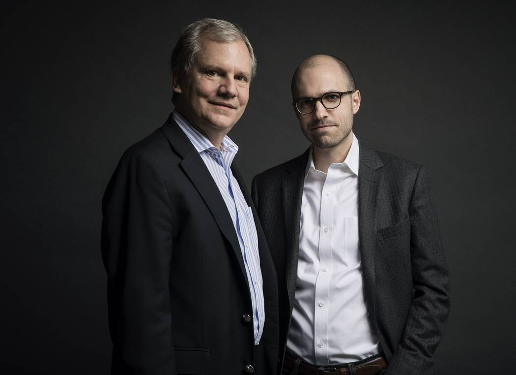 In this Dec. 13, 2017 photo, Arthur O. Sulzberger Jr., left, poses with his son, Arthur Gregg Sulzberger, on the 16th floor of the New York Times building in New York. The New York Times announced ...