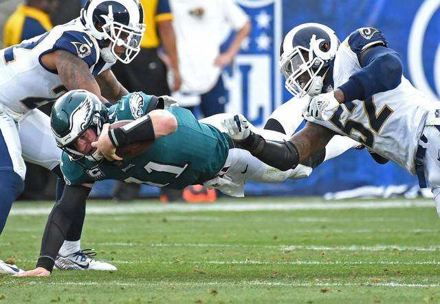 Dec 10, 2017; Los Angeles, CA, USA; Philadelphia Eagles quarterback Carson Wentz (11) is stopped by Los Angeles Rams inside linebacker Alec Ogletree (52) after a five yard gain in the third quarte ...
