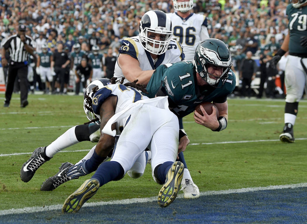 Philadelphia Eagles quarterback Carson Wentz gets tackles during the second half of an NFL football game against the Los Angeles Rams Sunday, Dec. 10, 2017, in Los Angeles. Wentz left the game sho ...