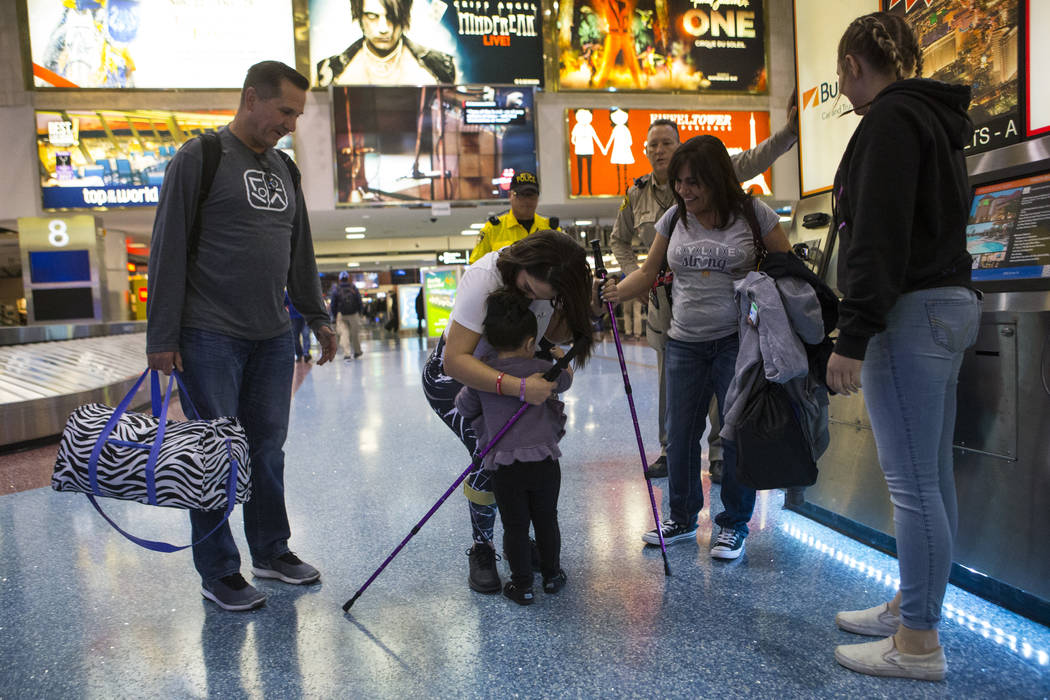 Two-year-old Valentina Sapone, center, gets a hug from her cousin Rylie Golgart, 19, upon her arrival at McCarran International Airport in Las Vegas on Friday, Dec. 15, 2017. Golgart, a victim in  ...