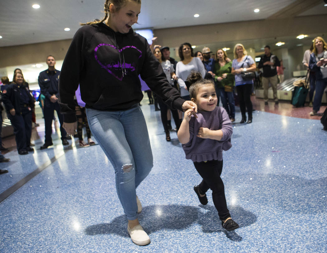 Riley Cress, left, runs with Valentina Sapone, 2, to see Rylie Golgart, 19, upon her arrival at McCarran International Airport in Las Vegas on Friday, Dec. 15, 2017. Golgart, a victim in the Oct.  ...