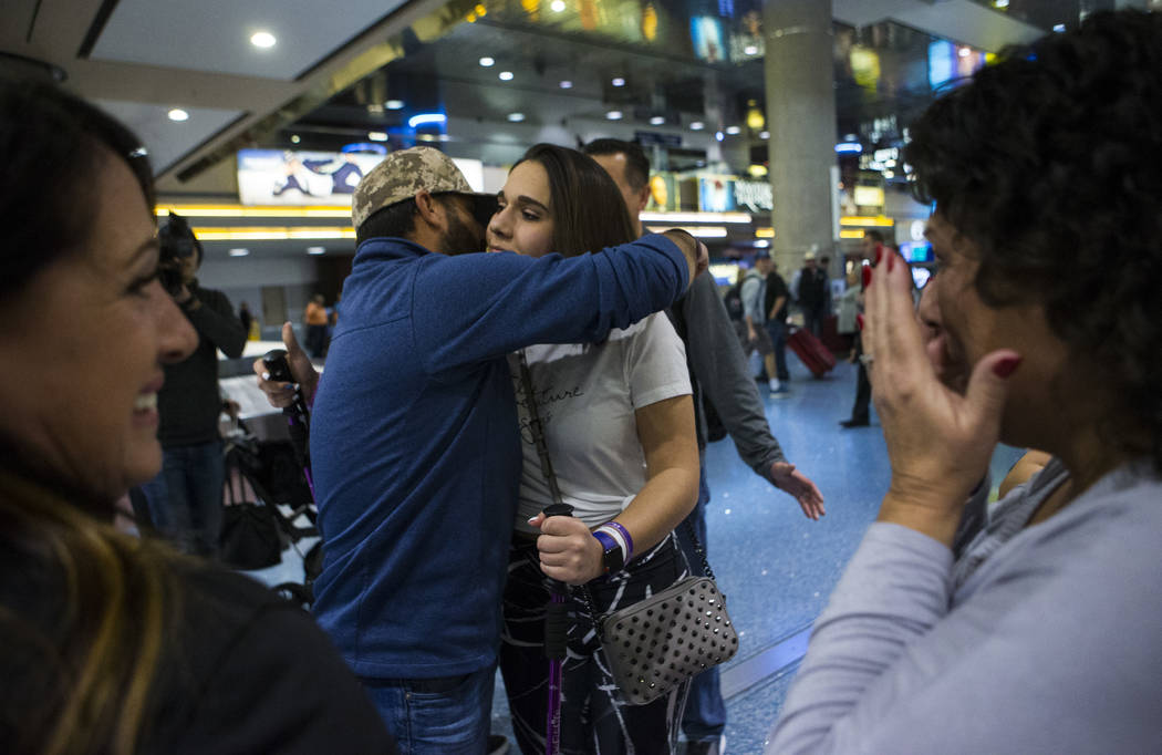 Nineteen-year-old Rylie Golgart gets a hug from her cousin Nick Bonifatto at McCarran International Airport in Las Vegas on Friday, Dec. 15, 2017. Golgart, a victim in the Oct. 1 shooting, spent t ...