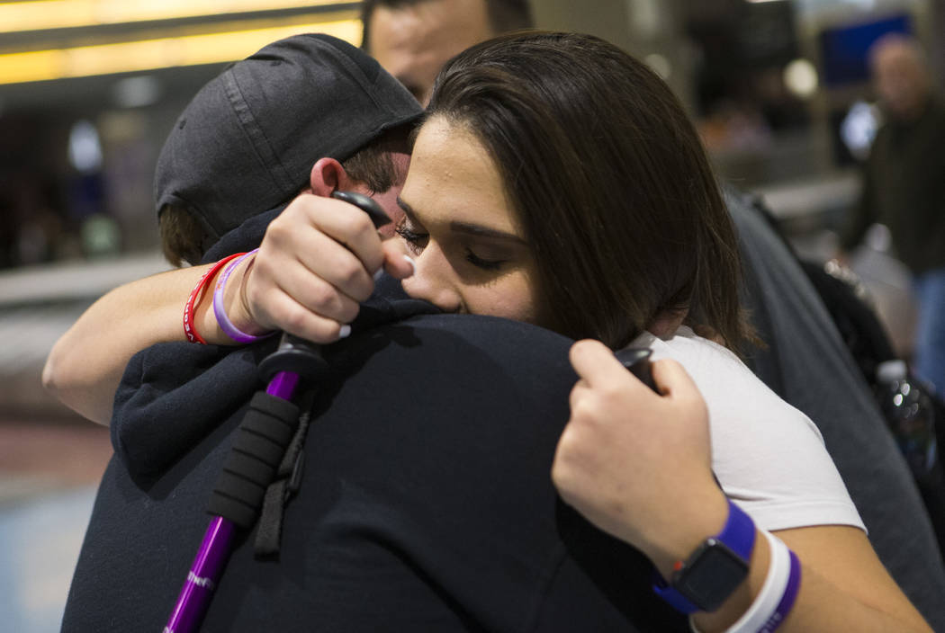 Nineteen-year-old Rylie Golgart embraces her boyfriend Cody Dion at McCarran International Airport in Las Vegas on Friday, Dec. 15, 2017. Golgart, a victim in the Oct. 1 shooting, spent two months ...