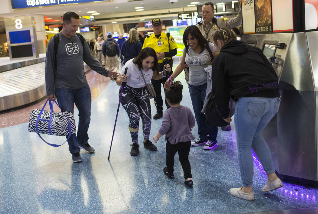 Two-year-old Valentina Sapone, center, walks up to greet her cousin Rylie Golgart, 19, upon her arrival at McCarran International Airport in Las Vegas on Friday, Dec. 15, 2017. Golgart, a victim i ...