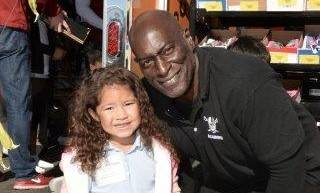 Reggie Kinlaw, a Raiders nose tackle from 1979 to 1984, poses with a girl who was among the 400 students at Rex Bell Elementary in Las Vegas to receive a free pair of shoes on Dec. 8, 2017. Courte ...
