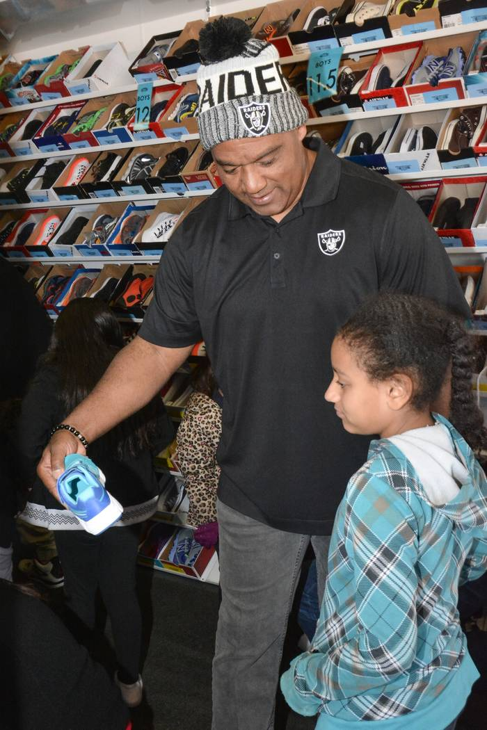 Chris McAlister assists a child who was part of the Raiders' shoe giveaway in Las Vegas. The Raiders teamed up with Goodie Two Shoes Foundation to give away 400 Pairs of shoes to Las Vegas childre ...