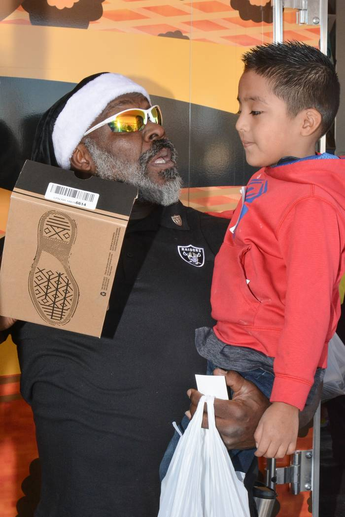 Roy Hart assists a child who was part of the Raiders' shoe giveaway in Las Vegas. The Raiders teamed up with Goodie Two Shoes Foundation to give away 400 Pairs of shoes to Las Vegas children on De ...
