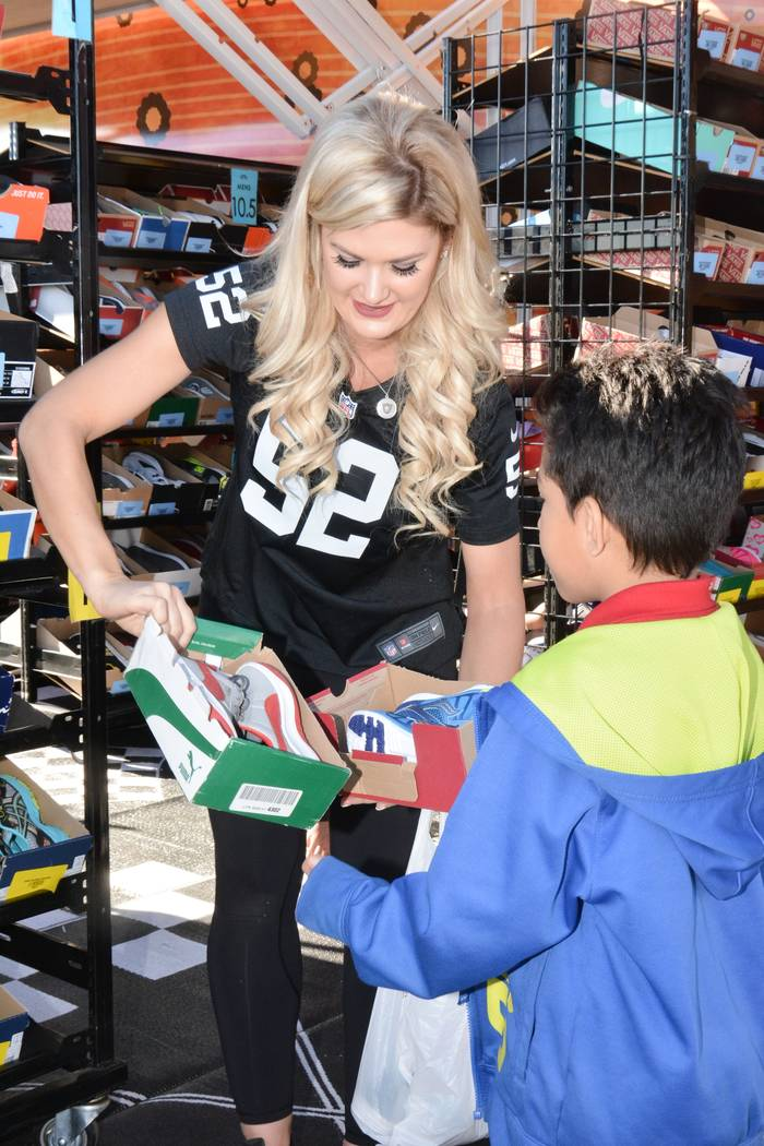 A Raiderette is seen helping a child who was part of the Raiders' shoe giveaway in Las Vegas. The Raiders teamed up with Goodie Two Shoes Foundation to give away 400 Pairs of shoes to Las Vegas ch ...