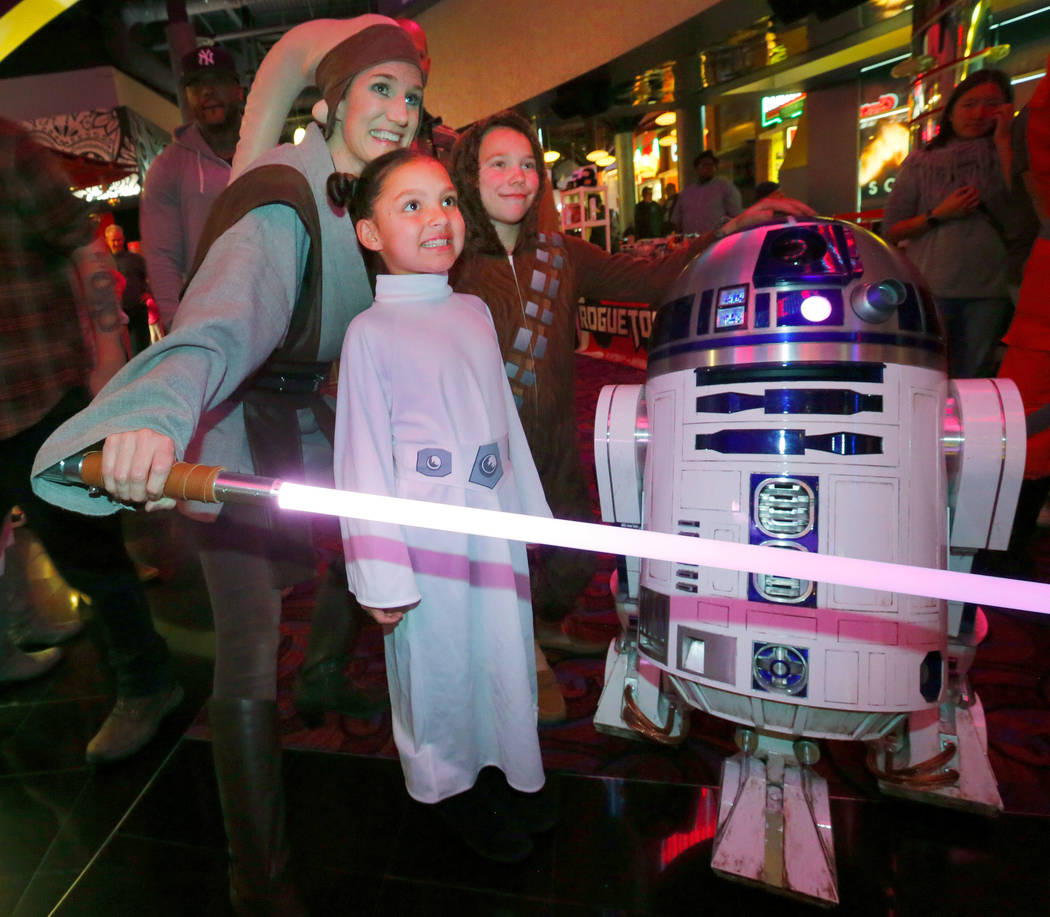 Dakota Wiegand, 7, of Las Vegas, dressed as Princess Leia center, and her brother Brice Foster, 9, dressed as Chewbacca, right, pose for a photo with Mary Nocie of the Rebel Legion dressed as Twi' ...