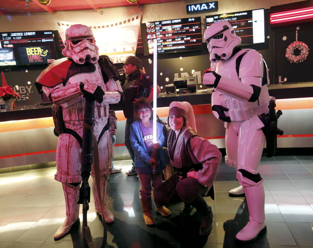 Leland Gonzalez, 5, of Las Vegas, second from left, poses for a photo with Mary Nocie of the Rebel Legion dressed as Twi'lek Jedi and Stormtroopers during the opening night fan event of Star Wars: ...