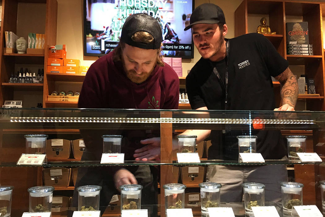 Torrey Holistics employees, Matt Sullivan, left, and Taron McElroy, arrange jars of cannabis in San Diego, Calif., Thursday, Dec. 14, 2017.  On Thursday, California issued its first batch of busin ...