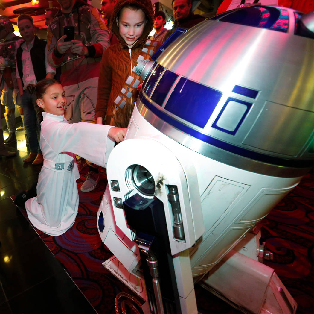 Dakota Wiegand, 7, of Las Vegas, dressed as Princess Leia and her brother Brice Foster, 9, dressed as Chewbacca, right, greet R2-D2 during the opening night fan event of Star Wars: The Last Jedi a ...