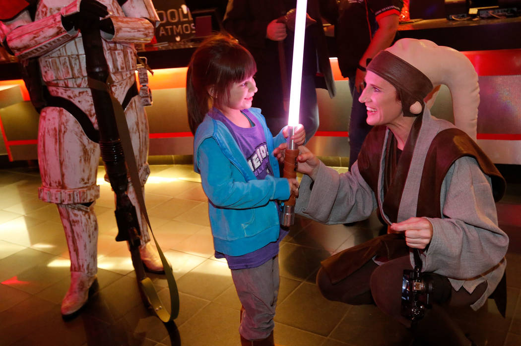 Leland Gonzalez, 5, of Las Vegas, left, talks with Mary Nocie of the Rebel Legion dressed as Twi'lek Jedi during the opening night fan event of Star Wars: The Last Jedi at Brenden Theatres at the  ...