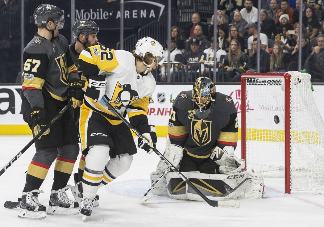 Golden Knights goaltender Marc-Andre Fleury (29) makes a save against Penguins left wing Carl Hagelin  (62) during the second period of Vegas' home matchup with Pittsburgh on Thursday, Dec. 14, 20 ...