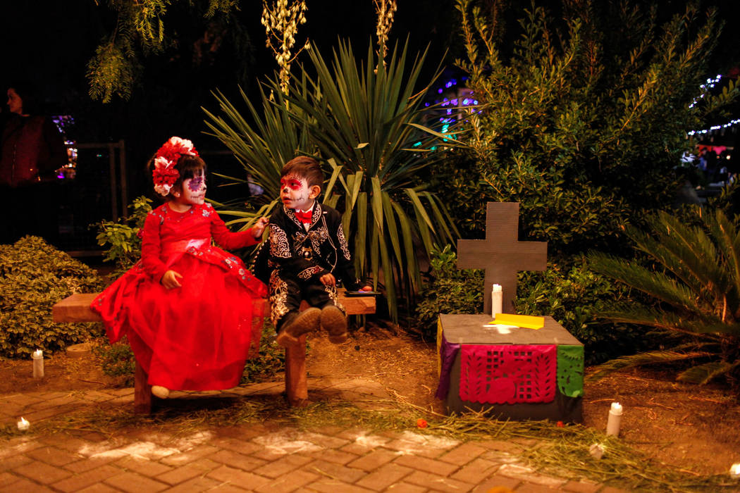 Ariel Torres, 4, left, and Leander Martinez, 4, right, both of Las Vegas, sit next to an altar during a Dia de los Muertos event at Springs Preserve in Las Vegas, Sunday, Nov. 5, 2017. Joel Angel  ...