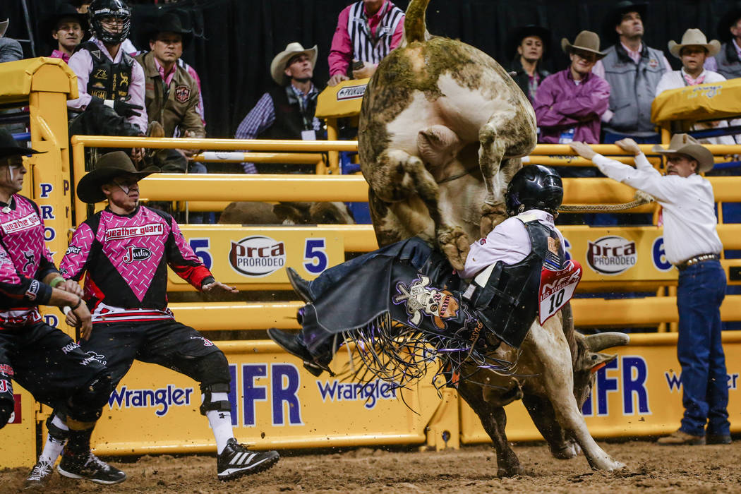 Garrett Smith of Rexburg, Idaho is kicked by More Big Bucks in the bull riding event during the fifth night of the 59th Wrangler National Finals Rodeo at the Thomas & Mack Center in Las Vegas, ...