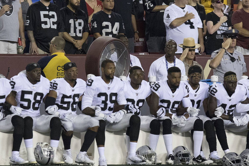 36f83064 Some of the Oakland Raiders interlock arms and sit during the national  anthem before their game