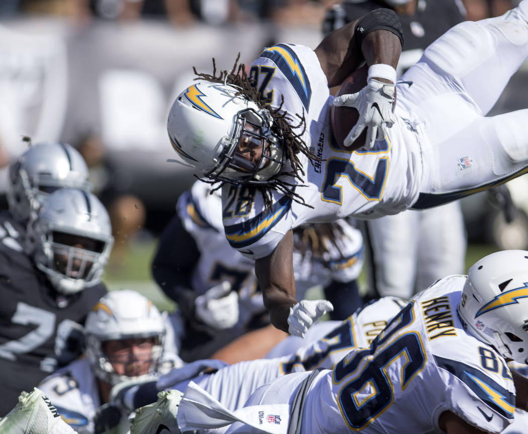 Los Angeles Chargers running back Melvin Gordon (28) launches himself over the goal line to score a touchdown during the first half of their game against the Oakland Raiders in Oakland, Calif., Su ...
