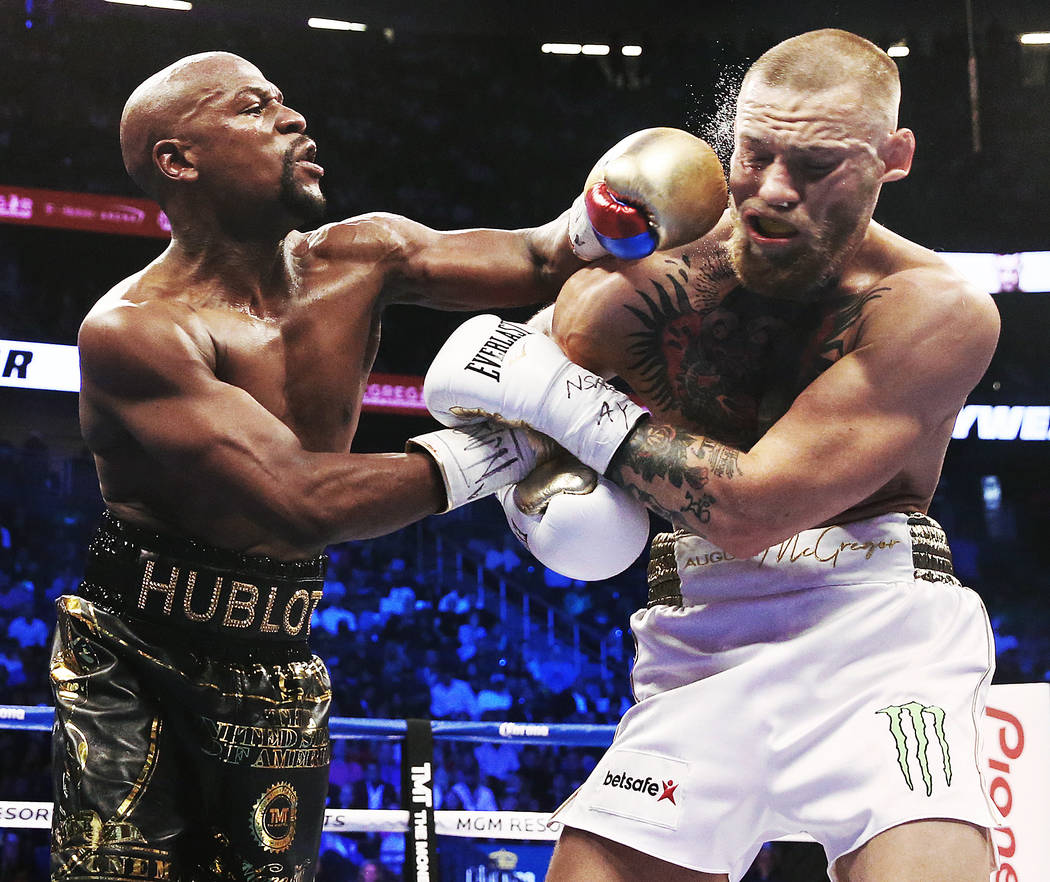 Floyd Mayweather, left, lands a left hook on the jaw of Conor McGregor on Saturday, Aug 26, 2017, at T-Mobile Arena, in Las Vegas. Mayweather defeated McGregor by technical knockout in the 10th ro ...