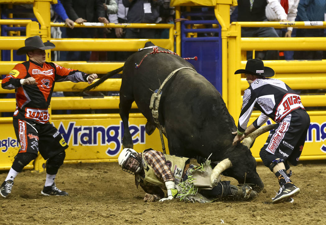 Jordan Spears of Redding, California is charged by El Patron in the bull riding competition during the eighth go-round of the National Finals Rodeo, Thursday, Dec. 14, 2017, at the Thomas & Ma ...