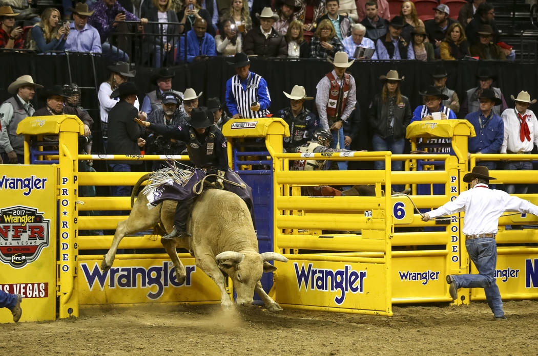 Tim Bingham of Honeyville, Utah comes out of the gate on Yellow Fever in the bull riding competition during the eighth go-round of the National Finals Rodeo, Thursday, Dec. 14, 2017, at the Thomas ...