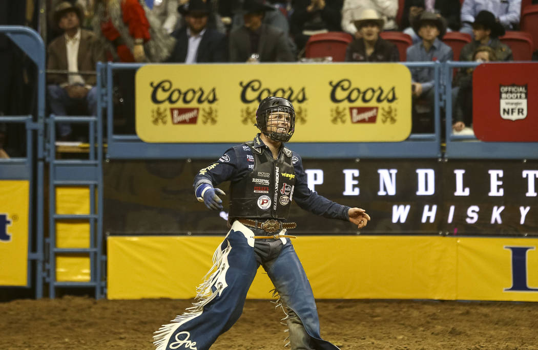 Joe Frost of Randlett, Utah reacts after riding Blizzard in the bull riding competition during the eighth go-round of the National Finals Rodeo, Thursday, Dec. 14, 2017, at the Thomas & Mack C ...