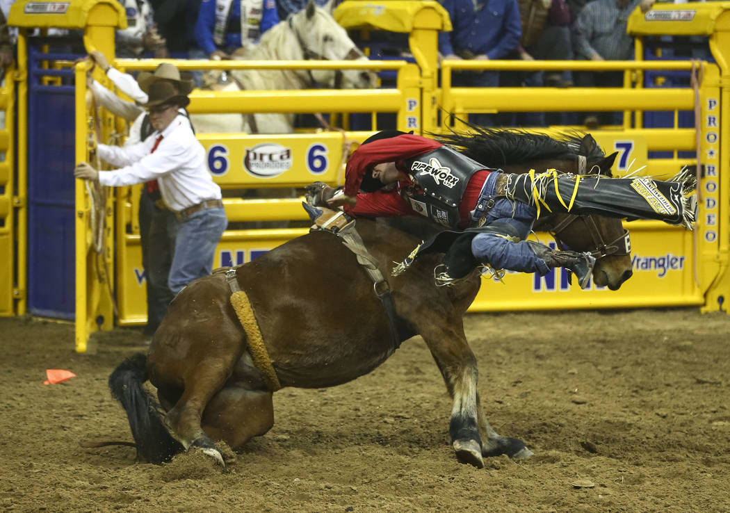 Jake Vold of Alberta, Canada gets hung up after getting bucked from Redigo in the bareback riding competition during the eighth go-round of the National Finals Rodeo, Thursday, Dec. 14, 2017, at t ...