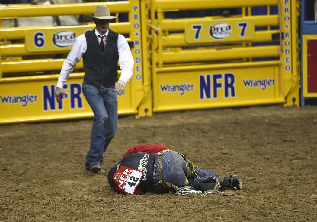 Jake Vold of Alberta, Canada lays on the dirt after getting hung up on Redigo in the bareback riding competition during the eighth go-round of the National Finals Rodeo, Thursday, Dec. 14, 2017, a ...