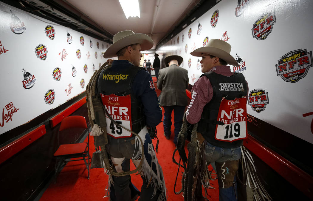 Professional bull riders Joe Frost of Utah (45) and Boudreaux Campbell of Texas (119) talk as they leave the arena following the bull riding competition in the eighth go-round of the National Fina ...