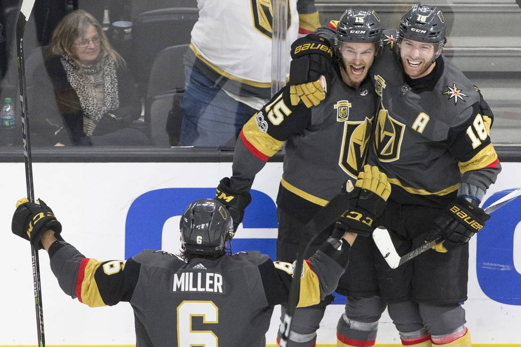 Golden Knights defenseman Jon Merrill (15) celebrates with teammates James Neal (18) and Colin Miller (6) after scoring the game winning goal in the third period during Vegas' home matchup with th ...