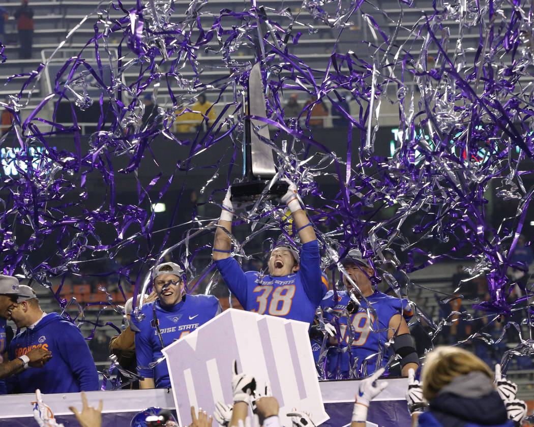 Boise State linebacker Leighton Vander Esch (38), with quarterback Brett Rypien, left, and offensive linesman Mason Hampton (59), holds up the trophy after the team's 17-14 win over Fresno State i ...
