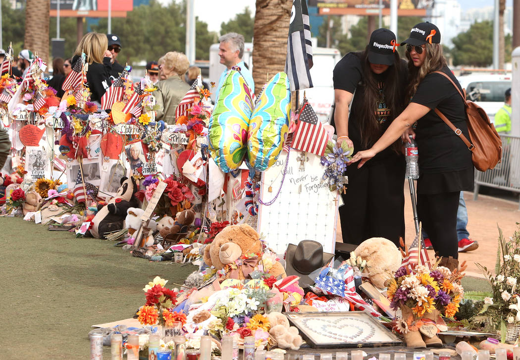 Las Vegas shooting survivors, including Lulu Farina, right, visit the Route 91 Harvest memorial at the Welcome to Fabulous Las Vegas sign Sunday, Nov. 12, 2017, in Las Vegas. Fifty eight crosses a ...