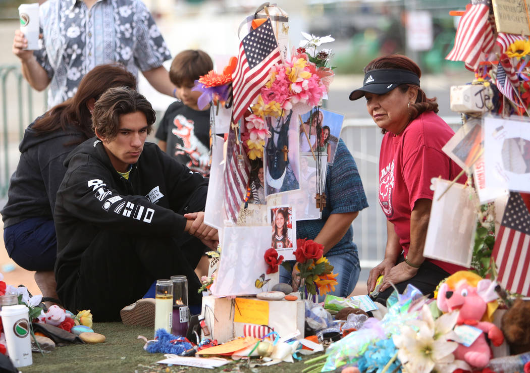 Matthew Ferandell, left, visits the cross of his cousin Angela Gomez at the Route 91 Harvest memorial at the Welcome to Fabulous Las Vegas sign Sunday, Nov. 12, 2017, in Las Vegas. Fifty eight cro ...