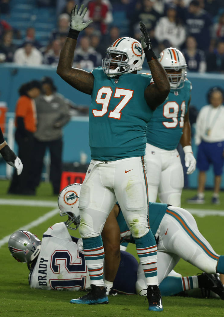 Miami Dolphins defensive tackle Jordan Phillips (97) celebrates after sacking New England Patriots quarterback Tom Brady (12), during the first half of an NFL football game, Monday, Dec. 11, 2017, ...
