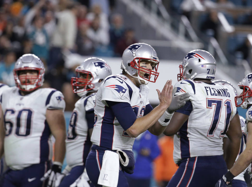 New England Patriots quarterback Tom Brady (12) cheers the offensive line on the field, during the second half of an NFL football game against the Miami Dolphins, Monday, Dec. 11, 2017, in Miami G ...