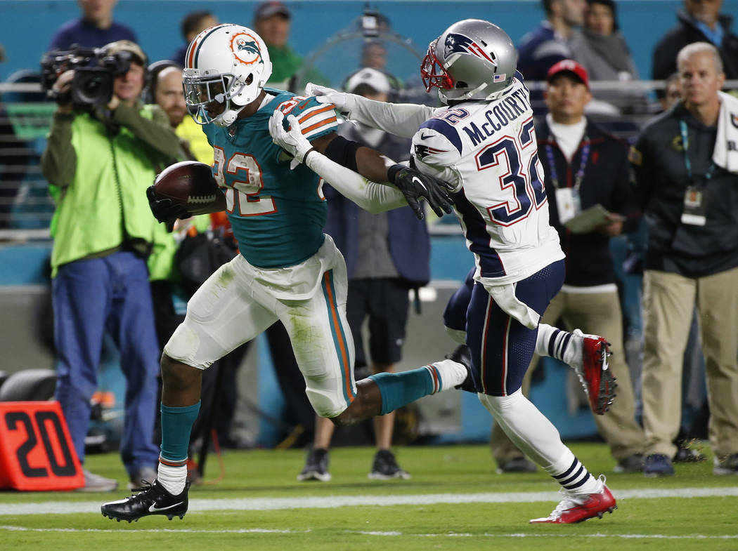 New England Patriots free safety Devin McCourty (32) attempts to stop Miami Dolphins running back Kenyan Drake (32), during the second half of an NFL football game, Monday, Dec. 11, 2017, in Miami ...