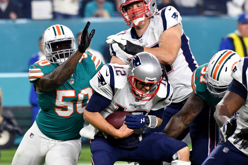 Dec 11, 2017; Miami Gardens, FL, USA; New England Patriots quarterback Tom Brady (12) is sacked by Miami Dolphins defensive end Andre Branch (50) during the second half at Hard Rock Stadium. Manda ...