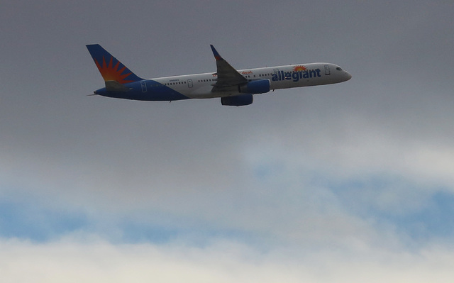 An Allegiant Air plane flies under a gray sky. Bizuayehu Tesfaye/Las Vegas Review-Journal Follow @bizutesfaye