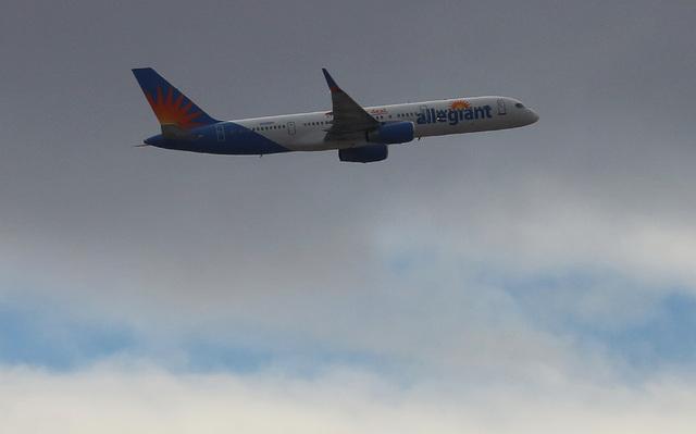 An Allegiant Air plane flies under a gray sky. Bizuayehu Tesfaye/Las Vegas Review-Journal Follow @bizutesfaye