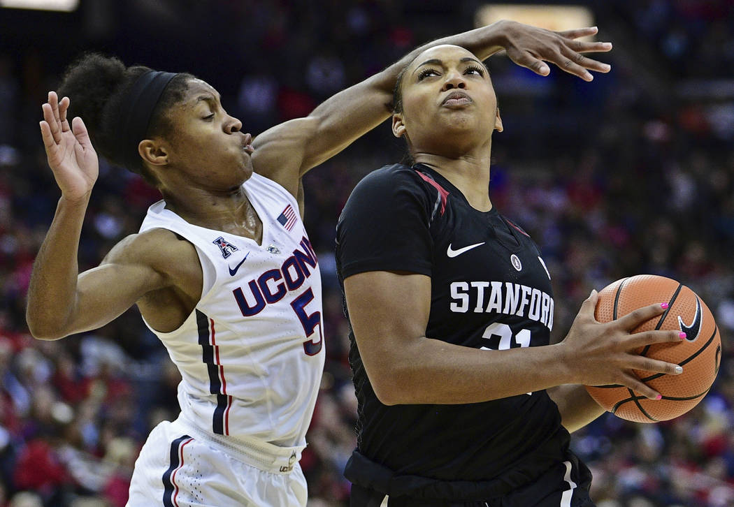 Stanford's DiJonai Carrington drives on Connecticut's Crystal Dangerfield during an NCAA college basketball game, Sunday, Nov. 12, 2017, in Columbus, Ohio. Connecticut won 78-53. (AP Photo/David D ...