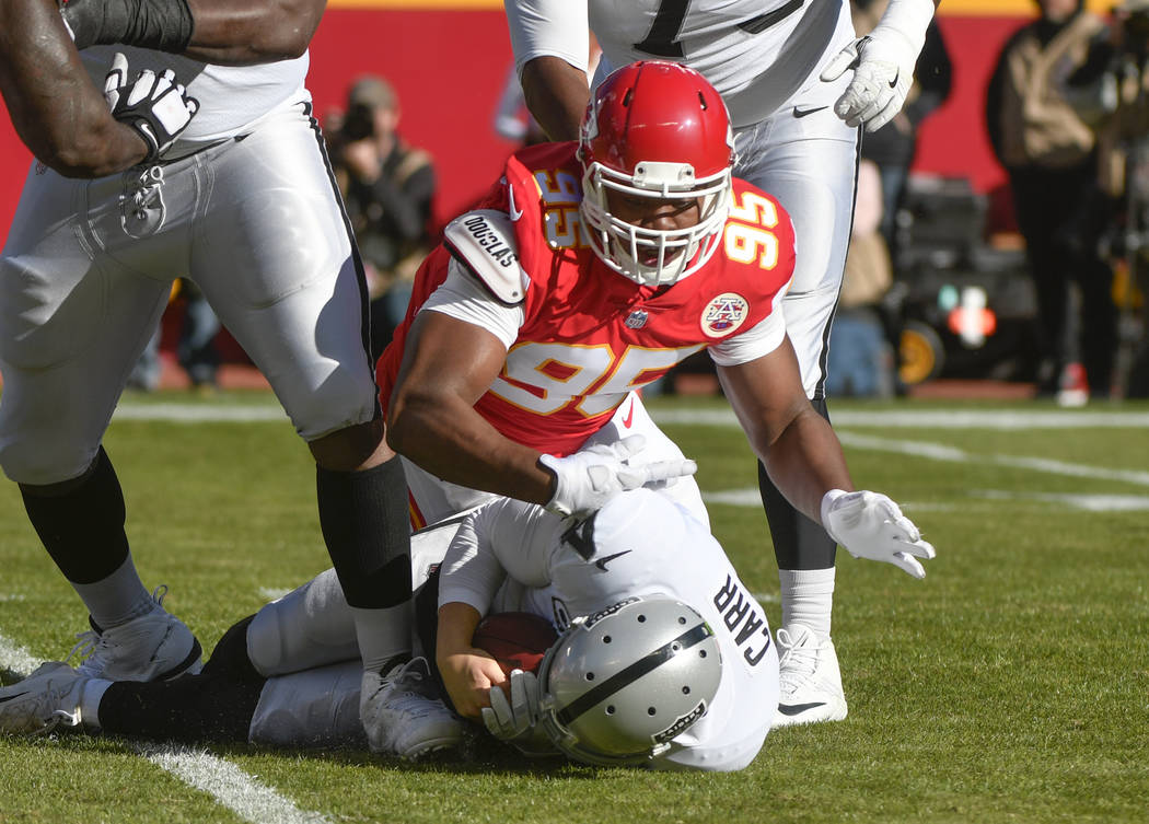Kansas City Chiefs defensive lineman Chris Jones (95) sacks Oakland Raiders quarterback Derek Carr (4) during the first half of an NFL football game in Kansas City, Mo., Sunday, Dec. 10, 2017. (AP ...
