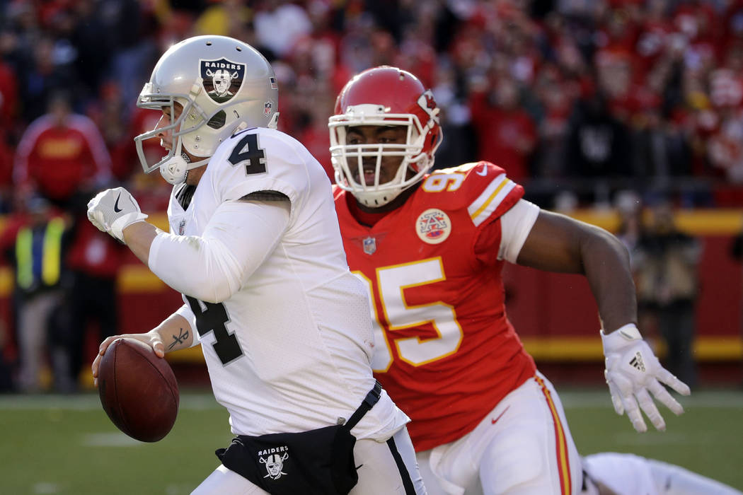 Oakland Raiders quarterback Derek Carr (4) is pursued by Kansas City Chiefs defensive lineman Chris Jones (95) during the second half of an NFL football game in Kansas City, Mo., Sunday, Dec. 10,  ...
