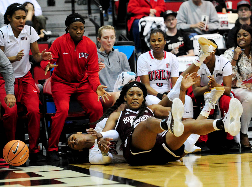 Mississippi State's Victoria Vivians and UNLV's Jordyn Bell collide out of bounds after chasing a loose ball during their NCAA women's college basketball game at Cox Pavilion in Las Vegas, Wednesd ...