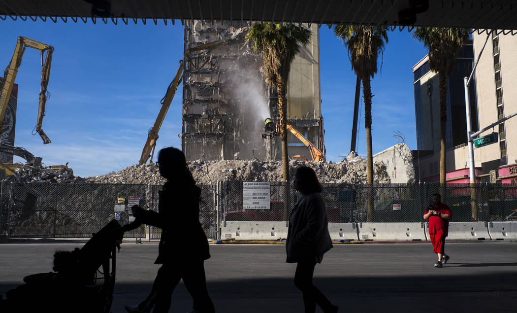 Pedestrians pass by as the demolition of the Las Vegas Club continues in downtown Las Vegas on Friday, Dec. 15, 2017. The property was purchased by Derek and Greg Stevens in 2015. Chase Stevens La ...