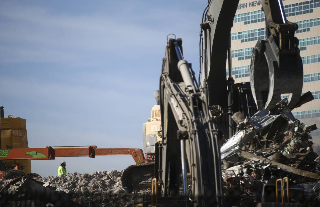 A construction worker is dwarfed by heavy equipment as the demolition of the Las Vegas Club continues in downtown Las Vegas on Friday, Dec. 15, 2017. The property was purchased by Derek and Greg S ...