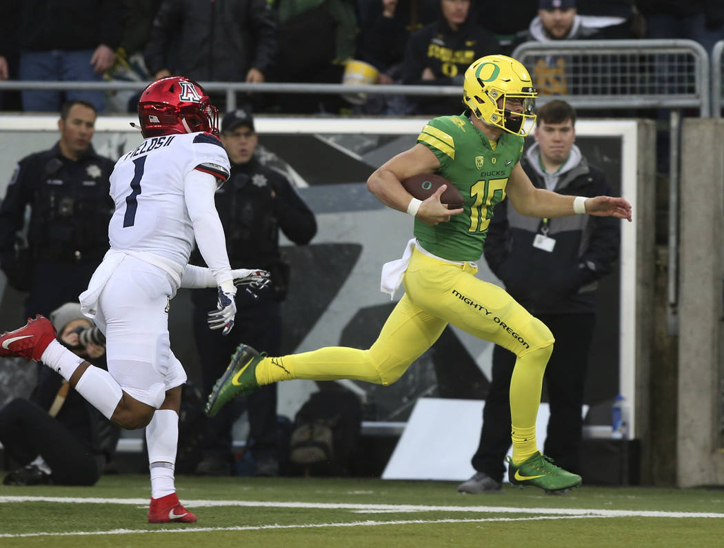 Oregon's quarterback Justin Herbert, right, rushes for the end zone ahead of Arizona's Tony Fields II for a touchdown during the first quarter of an NCAA college football game, Saturday, Nov. 18,  ...