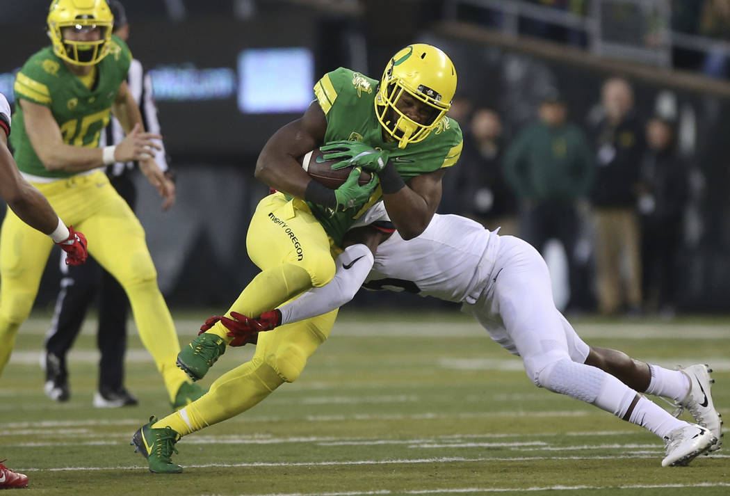 Oregon running back Royce Freeman, center left, is tackled by Arizona's Gavin Robertson Jr. during the first quarter of an NCAA college football game, Saturday, Nov. 18, 2017, in Eugene, Ore. (AP  ...